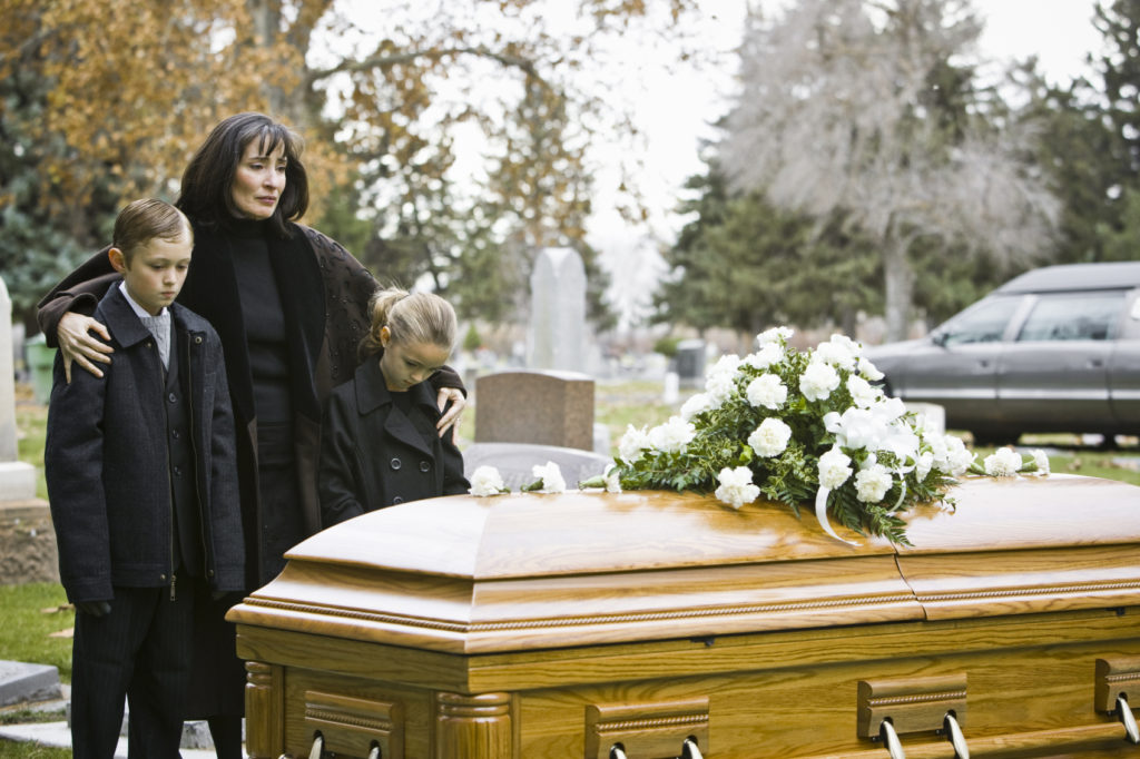A woman and her two children mourning at the casket of her deceased husband, who was killed in a wrongful death accident